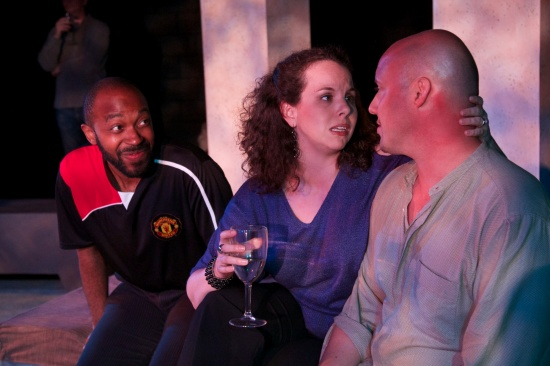 At the party: British Mark (Thaddaeus Edwards) and Collin (Chris Burner) dish with Tam (Amber Wood). Photo: Alan Dehmer.