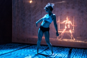 Nicola Bullock dancing as Khala, while Mia (Caitlin Wells) suffers in sequestration behind the scrim. Photo: Alex Maness.