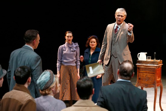 The Ensemble (Allison Altman as Petra, Julia Gibson as Mrs. Catherine Stockmann and Michael Bryan French as Dr. Stockmann, facing) in PlayMakers Repertory Company's production of AN ENEMY OF THE PEOPLE,  by Henrik Ibsen, adapted by Arthur Miller. Photo by Jon Gardiner.